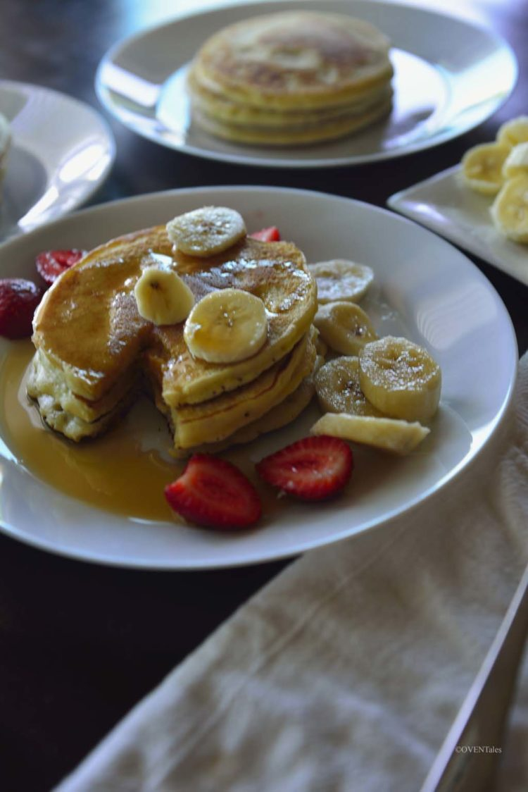 Pancake stack on a white plate with syrup and slices of banana and strawberries.