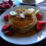 Image for pinning - stack of pancakes on a white plate with syrup and sliced fruit on it.